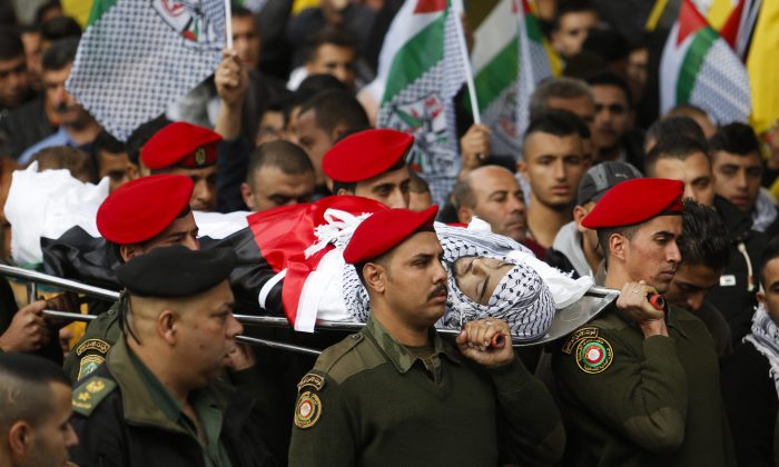 Palestinian security officers carry the body of 16-year-old Ibrahim Dawood during his funeral in the West Bank city of Ramallah, Thursday, Nov. 26, 2015. (AP Photo/Nasser Shiyoukhi)