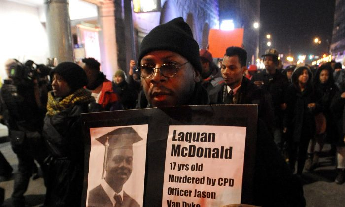A protester holds a sign as people rally for 17-year-old Laquan McDonald, who was shot 16 times by Chicago Police Department Officer Jason Van Dyke in Chicago, on Nov. 24, 2015. (AP Photo/Paul Beaty)