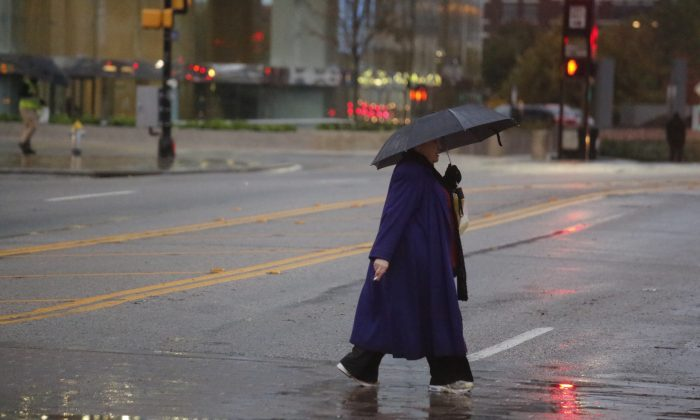 A pedestrian tries to stay dry as she crosses Lamar St at Pacific Ave in downtown Dallas Friday, Nov. 27, 2015. A cold front hit the Dallas Fort Worth area early bringing cold weather and rain. (Ron Baselice /The Dallas Morning News via AP) MANDATORY CREDIT; MAGS OUT; TV OUT; INTERNET USE BY AP MEMBERS ONLY; NO SALES