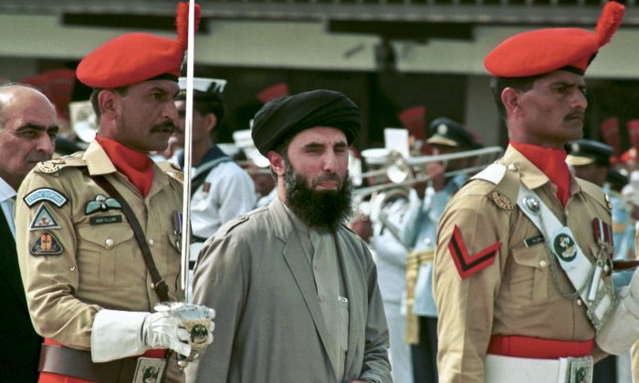 In this Wednesday, June 26, 1996 file photo, Gulbuddin  Hekmatyar, center, passes in front of an honor guard in the Afghan capital of Kabul, Afghanistan.  (AP Photo)