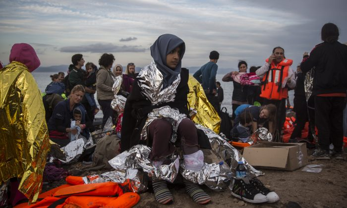 """Refugees are helped by volunteers after crossing the Aegean sea on a dinghy from the Turkey's coast to the northeastern Greek island of Lesbos, on Tuesday, Nov. 24, 2015. Several European countries, including EU members Slovenia and Croatia and non-members Serbia and Macedonia, have declared they will only allow """"war-zone refugees"""" from Afghanistan, Iraq and Syria to transit through their countries on their way to central and northern Europe. (AP Photo/Santi Palacios)"""