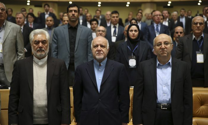 Iran's Oil Minister Bijan Zanganeh (C), Managing Director of National Iranian Oil Company, Roknoddin Javadi (R), head of parliament's energy committee Ali Marvi (L), and participants listen to Iran's national anthem during opening ceremony of Iran Petroleum Contracts Conference in Tehran, Iran, Saturday, Nov. 28, 2015. Iran has unveiled a new model of oil contracts aimed at attracting foreign investment once sanctions are lifted under a landmark nuclear deal reached earlier this year. (AP Photo/Vahid Salemi)