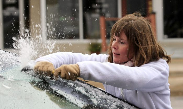 Krystal Wright scrapes ice from her car's windshield in Wichita, Kan., Friday, Nov. 27, 2015. The winter weather left a layer of ice on roads and cars early Friday morning after a heavy rain on Thanksgiving day that set a record with over 2 inches of rain. Brian Corn/The Wichita Eagle via AP)