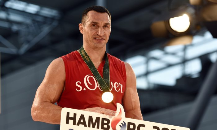 Ukrainian World boxing champion Wladimir Klitschko promotes Hamburg's bid for Olympic Games in 2024 during a public training session at the airport in Duesseldorf, Germany, prior his heavyweight boxing fight against challenger Tyson Fury from Britain, Wednesday, Nov. 25, 2015. The title bout will take place in Duesseldorf's  LTU arena on Saturday.  Poster reads: Hamburg 2024, and : This is unique'. (AP Photo/Martin Meissner)