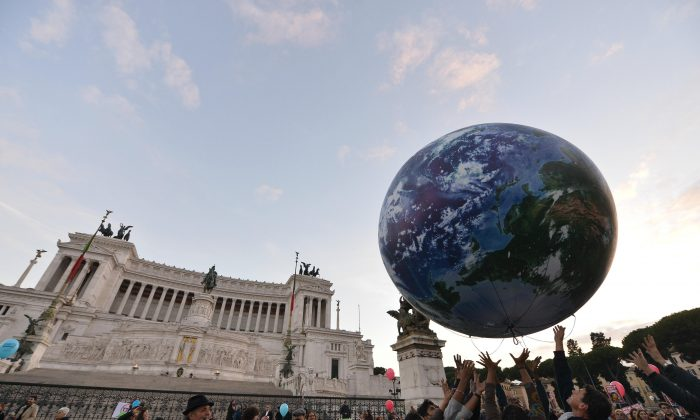 People play with a giant balloon representing Earth at Piazza Venezia during a rally calling for action on climate change on Nov. 29, 2015, in Rome a day before the launch of the COP21 conference in Paris. (Tiziana Fabi/AFP/Getty Images)