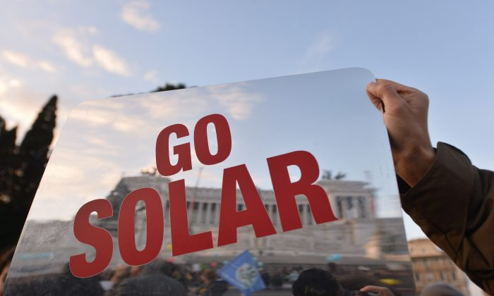 A man holds a placard reading 'Go Solar' during a rally calling for action on climate change on Nov. 29, 2015, in Rome a day before the launch of the COP21 conference in Paris. (Tiziana Fabi/AFP/Getty Images)