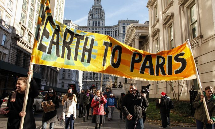 People hold a banner as they take part in a global climate march near City Hall on Nov. 29, 2015, in New York City. The protest is part of an international weekend of action that is being mobilized to support climate activists in Paris whose massive march has been prevented by French authorities due to the recent attacks. Around 570,000 people have already marched in 2,300 events in 175 countries around the world. (Kena Betancur/Getty Images)