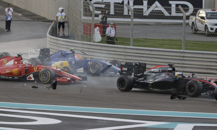 McLaren driver Fernando Alonso of Spain, second from right, , crashes with Lotus driver Pastor Maldonado of Venezuela as Ferrari driver Sebastian Vettel of Germany, left, and Sauber driver Felipe Nasr of Brazil run during the Emirates Formula One Grand Prix at the Yas Marina racetrack in Abu Dhabi, United Arab Emirates, Sunday, Nov. 29, 2015. (AP Photo/Luca Bruno)