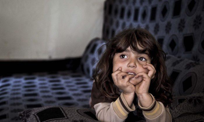 In this Saturday, Nov. 28, 2015 photo, Syrian refugee Simav Nuh, rests inside an informal tented settlement in Irbil, northern Iraq.  (AP Photo/Seivan M. Salim)