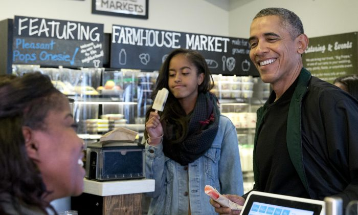 President Barack Obama, joined by his daughters Malia (L) and Sasha, in the background at right, orders a treat at Pleasant Pops on Small Business Saturday in Washington, Saturday, Nov. 28, 2015. (AP Photo/Carolyn Kaster)