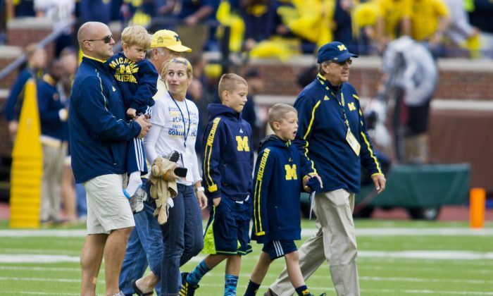 In this Sept. 12, 2015, file photo, former Michigan coach Lloyd Carr, far right, leads his grandsons T.J. and Tommy Carr, daughter-in-law Tammi Carr, and son Jason Carr, far left, holding his son Chad Carr, onto the Michigan Stadium field for the pregame coin toss, before an NCAA college football game against Oregon State in Ann Arbor, Mich. The 5-year-old grandson of former Michigan football coach Lloyd Carr has died more than a year after he was diagnosed with a rare, inoperable form of brain cancer. Chad Carr's father, Jason Carr, says his son died Monday, Nov. 23, 2015, in the family's Pittsfield Township home, where the boy had recently entered hospice care.  (AP Photo/Tony Ding, File)