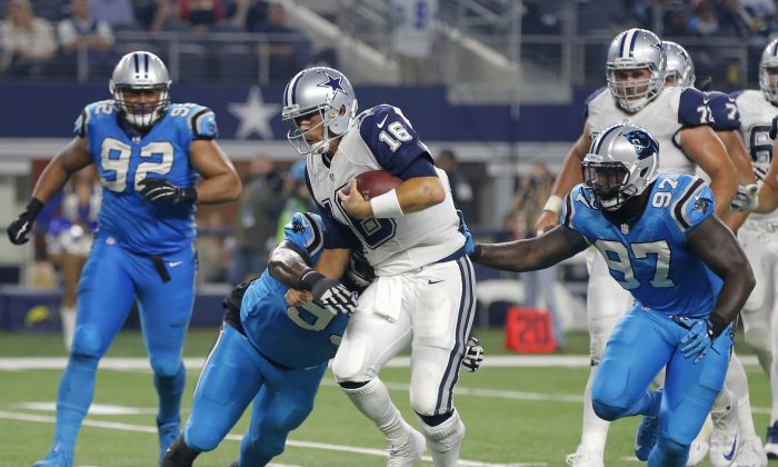 Dallas Cowboys quarterback Matt Cassel (16) is tackled by Carolina Panthers' Kyle Love (93) and Mario Addison (97) as Dwan Edwards (92) watches during the second half of an NFL football game Thursday, Nov. 26, 2015, in Arlington, Texas. (AP Photo/Brandon Wade)