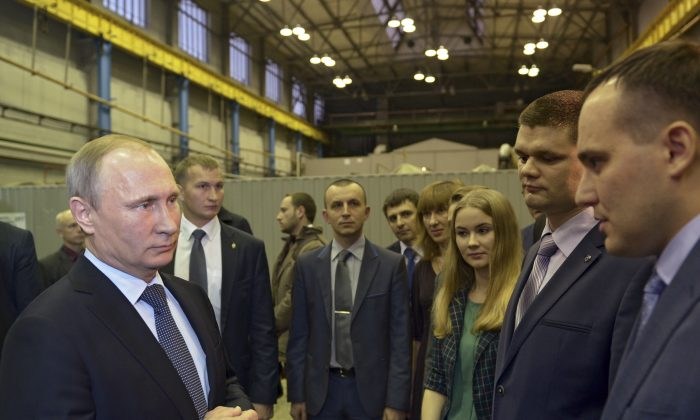 Russian President Vladimir Putin (L) meets with employees of the Ural Transport Machine Building Design Bureau during a visit to the UralVagonZavod factory in Nizhny Tagil in the Ural mountains, Russia, on Nov. 25, 2015. (Alexei Nikolsky/Sputnik via AP)