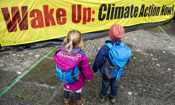 Two Children in front of a banner during a protest rally of the 'Climate Alliance Switzerland' in Zurich, Switzerland, on Nov. 28, 2015, ahead of the COP21 climate summit in Paris. (Anthony Anex/Keystone via AP)