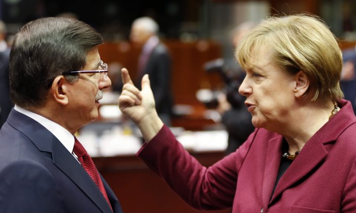 German Chancellor Angela Merkel talks to Turkish Prime Minister Ahmet Davutoglu during an EU-Turkey summit at the EU Council building in Brussels on Sunday, Nov. 29, 2015. (AP Photo/Michael Probst)