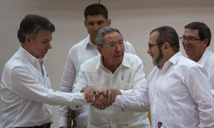 "Cuba's President Raul Castro, center, encourages Colombian President Juan Manuel Santos (L) and Commander the Revolutionary Armed Forces of Colombia or FARC, Timoleon Jimenez, known as  ""Timochenko"", to shake hands, in Havana, Cuba, on Sept. 23, 2015. (AP Photo/Desmond Boylan, File)"