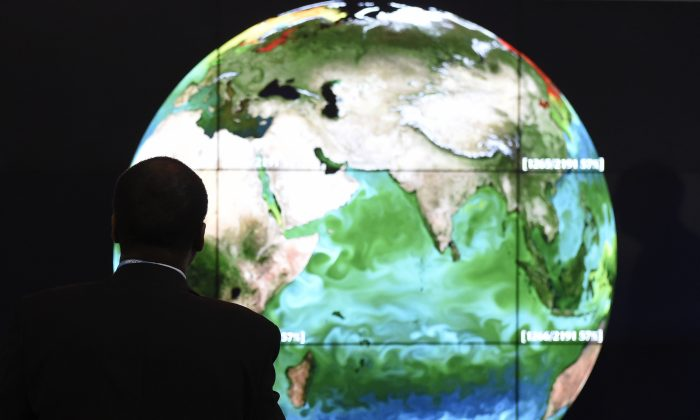 A conference attendee looks at a projection of the Earth on the opening day of the COP21 U.N. conference on climate change in Le Bourget, outside Paris, France, on Nov. 30, 2015. (Alain Jocard/AFP/Getty Images)