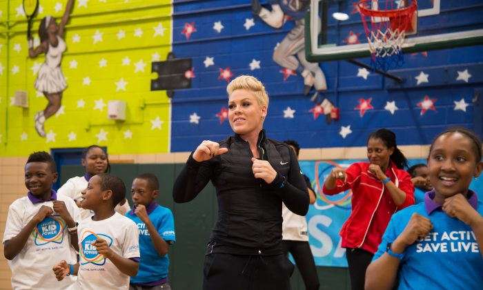 Singer Pink exercises with students from PS 242 Young Diplomats Magnet Academy at the launch of UNICEF Kid Power in New York on Monday, Nov. 30, 2015. (Charles Sykes/Invision via AP)