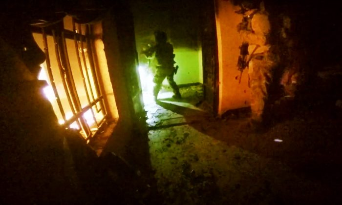 This image made from video taken on Thursday, Oct. 22, 2015 from a helmet camera, shows U.S. and Iraqi special forces freeing hostages from a prison controlled by Islamic State militants in the town of Huwija, 15 kilometers (9 miles) west of the Iraqi city of Kirkuk. (Kurdistan Regional Security Council via AP)
