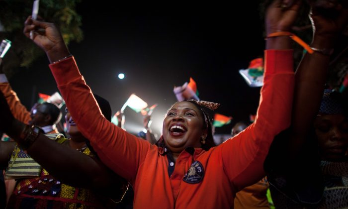 A supporter of presidential election candidate of Burkina Faso Roch Marc Christian Kabore celebrate after preliminary results showed him to be the winner of recent elections, supporters gather outside  Kabore's campaign headquarters  in Ouagadougou, Burkina Faso, Tuesday, Dec. 1, 2015. (AP Photo/Theo Renaut)
