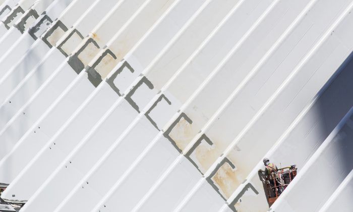 A worker paints the ribs of the World Trade Center transportation hub, designed by Spanish architect Santiago Calatrava, in New York, on June 25, 2015. U.S. construction spending jumped in October, fueled by solid gains in home building and the largest increase in federal construction in nine years, according to the Commerce Department, Tuesday, Dec. 1, 2015. (AP Photo/Mark Lennihan)