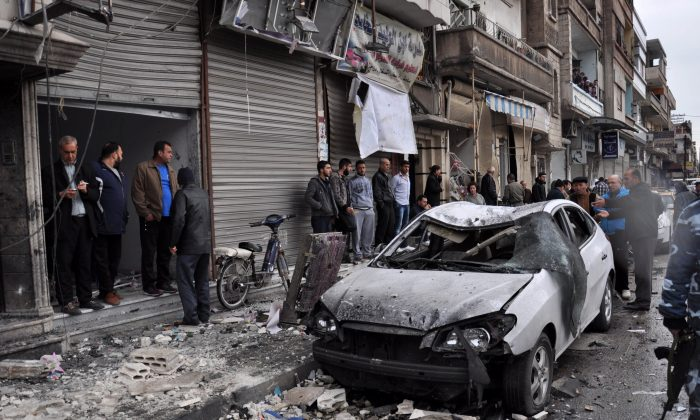 Syrian residents and security forces inspect the damage following a car bomb explosion on April 10, 2015, in the government-controlled majority Alawite neighbourhood of Hay al-Arman, located on the outskirts of the Zahraa district in Homs city. (AFP/Getty Images)