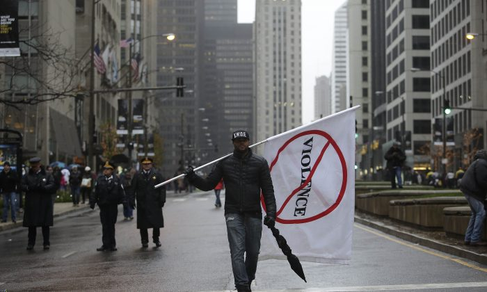 A demonstrator protesting the shooting of Laquan McDonald who was killed by a Chicago police Officer walks along Michigan Avenue also known as the Magnificent Mile in Chicago, Ill., on Nov. 27, 2015. (Joshua Lott/Getty Images)