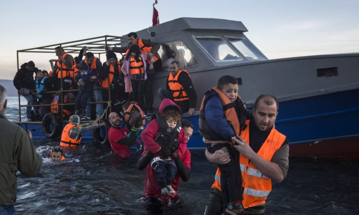 Volunteers help around 50 refugees and migrants to disembark from a vessel after their arrival from the Turkish coast to the northeastern Greek island of Lesbos, on Tuesday, Dec. 1, 2015. (AP Photo/Santi Palacios)