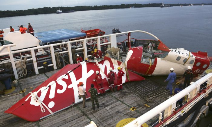 In this Sunday, Jan.11, 2015 file photo, crew members of Crest Onyx recovery ship prepare to unload the newly-recovered tail section of crashed AirAsia Flight 8501 at Kumai port in Pangkalan Bun, Central Borneo, Indonesia. (AP Photo/Achmad Ibrahim)