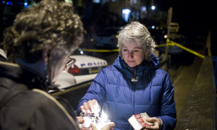 "D.J. Thomson (R) and Joyce Levine light candles on Kennedy Street after hearing about the death of Mayor Stephen ""Greg"" Fisk in Juneau, Alaska, on Nov. 30, 2015. (Michael Penn/The Juneau Empire via AP)"