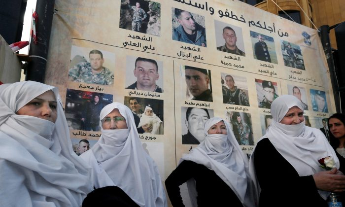 Lebanese Druze women stand next to posters with pictures of soldiers and policemen who were kidnapped by militants from the Islamic State and al-Qaida's branch in Syria, the Nusra Front, during a protest in downtown Beirut, Lebanon, Tuesday, Dec. 1, 2015. Syria's al-Qaida branch was releasing on Tuesday a group of Lebanese soldiers and policemen held captive since August 2014 as part of a swap deal brokered by Qatar that included Lebanon setting free an unspecified number of prisoners wanted by the militant group. (AP Photo/Bilal Hussein)