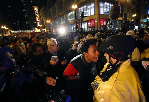 """Lamon Reccord, second from right, yells at a Chicago police officer """"Shoot me 16 times"""" as he and others march through Chicago's Loop Wednesday, Nov. 25, 2015, one day after murder charges were brought against police officer Jason Van Dyke in the killing of 17-year-old Laquan McDonald, in Chicago. (AP Photo/Charles Rex Arbogast)"""