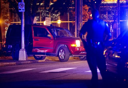 A police officer stands near the scene of an officer-involved shooting, Tuesday, Dec. 1, 2015, in Atlanta, that left one person dead in downtown on Monday. (AP Photo/David Goldman)