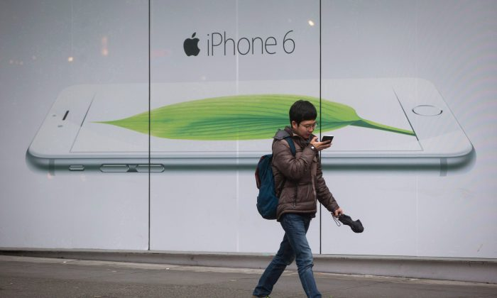 A man looks at his mobile phone while walking past an iPhone 6 advertisement outside the Telus headquarters in Vancouver on Dec. 18, 2014. Canadians are making fewer official complaints about their mobile phone plans but more about their Internet service, according to a new report. (The Canadian Press/Darryl Dyck)