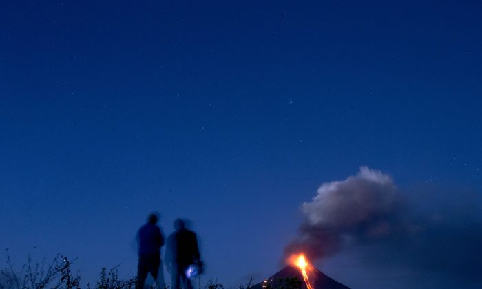 Nicaraguan Institute of Territorial Studies' employees watch from a distance the Momotombo volcano's eruption and lava flow, in the rural community of Papalonal, in Leon, Nicaragua, Wednesday, Dec, 2, 2015. Quiet for many years, the volcano emitted some glowing rock on Wednesday, after gas and ash emissions began Tuesday. In 1610, the city of Leon was destroyed during an eruption of the Momotombo and was relocated west, where it is currently located. (AP Photo/Esteban Felix)