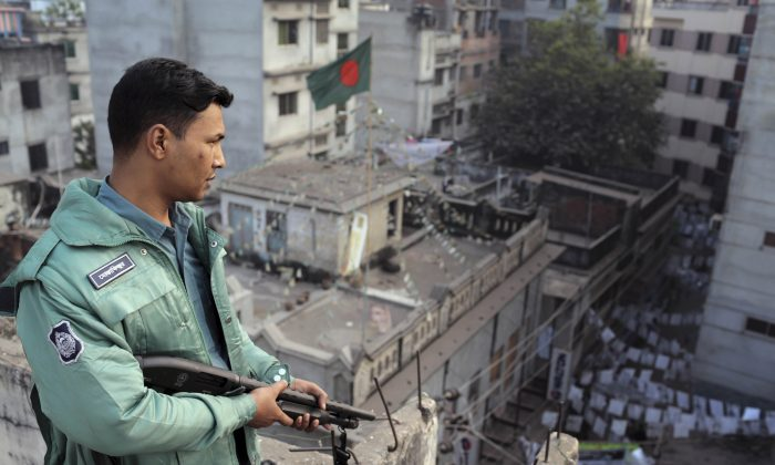 A Bangladeshi policeman stands guard on the rooftop of a polling center in Dhaka, Bangladesh, on Jan. 5, 2014. (AP Photo/A.M. Ahad)