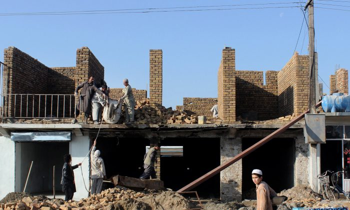 In this Tuesday, Dec. 1, 2015, photo, Afghan laborers rebuild a destroyed shop in Kunduz city, north of Kabul, Afghanistan. (AP Photo/Najim Rahim)