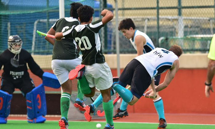 Will Glover of HKFC-A forces a way through the Pak-A defense to score goal number 3 in their 5-0 win at in the HKHA Premier Division Sports Road on Sunday Nov 29, 2015. (Bill Cox/Epoch Times)