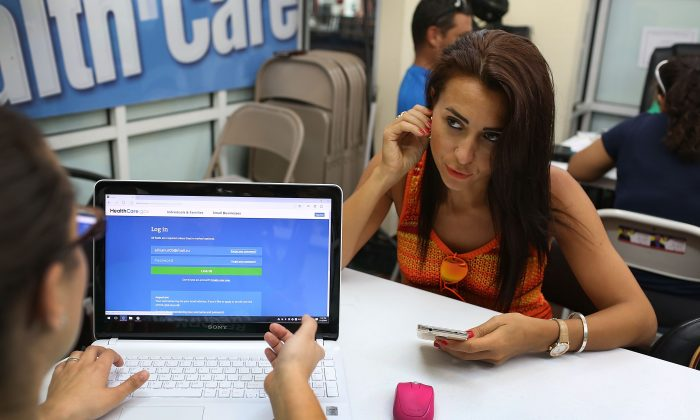 Alina Nurieva (R)  sits with Gabriela Cisneros, an insurance agent from Sunshine Life and Health Advisors, as she picks an insurance plan available in the third year of the Affordable Care Act at a store setup in the Mall of the Americas on November 2, 2015 in Miami, Florida. (Joe Raedle/Getty Images)