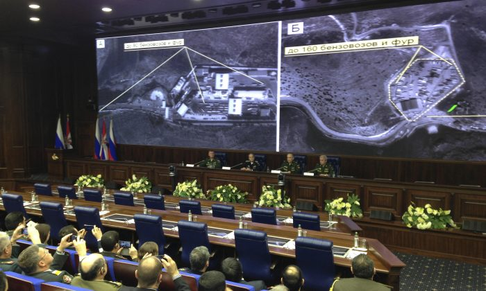 Russian top military officials speak to the media in front of an aerial images they say are oil trucks near Turkey's border with Syria displayed by the Russian Defense Ministry at a briefing in Moscow, Russia, Wednesday, Dec. 2, 2015. The Russian Defense Ministry invited dozens of foreign military attaches and hundreds of journalists to reveal what they said were satellite and aerial images of thousands of oil trucks streaming from the ISIS-controlled deposits in Syria and Iraq into Turkish sea ports and refineries. Russian Deputy Defense Minister Anatoly Antonov accused Turkish President Recep Tayyip Erdogan and his family of personally profiting from the oil trade with the Islamic State. (AP Photo/Vladimir Kondrashov)