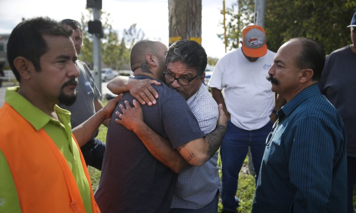 Jesus Gonzales, center left, who has been separated with his wife since Wednesday's shooting, is comforted by local church members including Jose Gomez, center right, Thursday, Dec. 3, 2015, in San Bernardino, Calif. (AP Photo/Jae C. Hong)