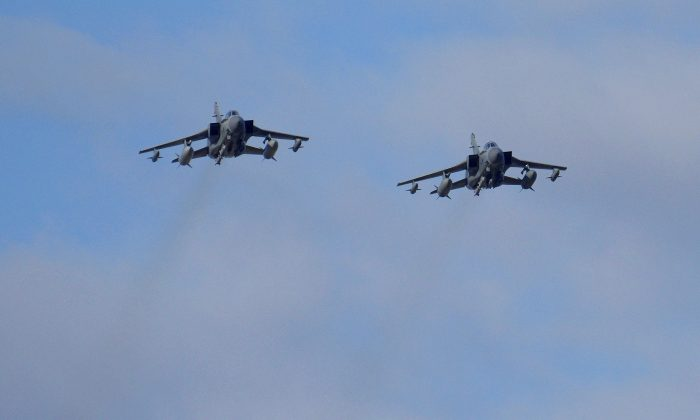 Two British Tornados warplanes fly over the RAF Akrotiri, a British air base near costal city of Limassol, Cyprus, Thursday, Dec. 3, 2015, as they arrive from an airstrike against Islamic State group targets in Syria. (AP Photo/Pavlos Vrionides)
