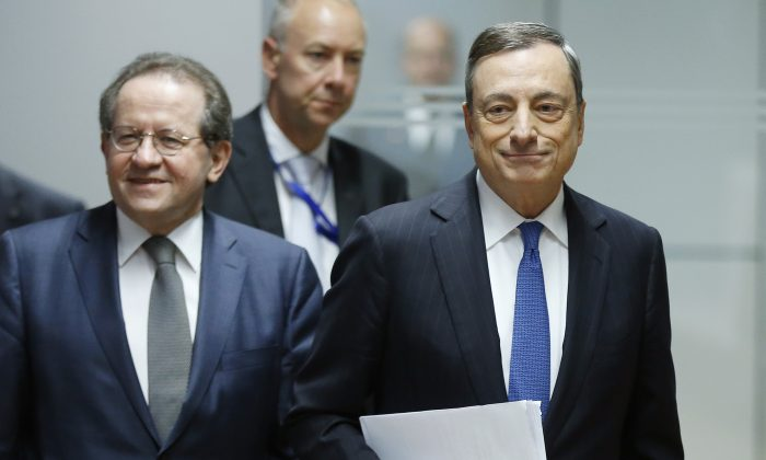 President of European Central Bank Mario Draghi (R) and vice president Vitor Constancio are on their way to a press conference following a meeting of the governing council in Frankfurt, Germany, Thursday, Dec. 3, 2015. (AP Photo/Michael Probst)