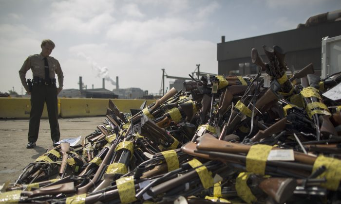A Los Angeles County Sheriffs deputy looks at a pile of guns during the destruction of approximately 3,400 guns and other weapons at the Los Angeles County SheriffsÕ 22nd annual gun melt at Gerdau Steel Mill on July 6, 2015 in Rancho Cucamonga, California. (David McNew/Getty Images)