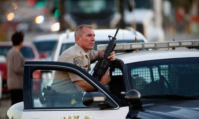 A California Highway Patrol officer stands with his weapon as authorities pursued the suspects in a shooting that occurred at the Inland Regional Center in San Bernardino, Calif., on Dec. 2, 2015. (Sean M. Haffey/Getty Images)