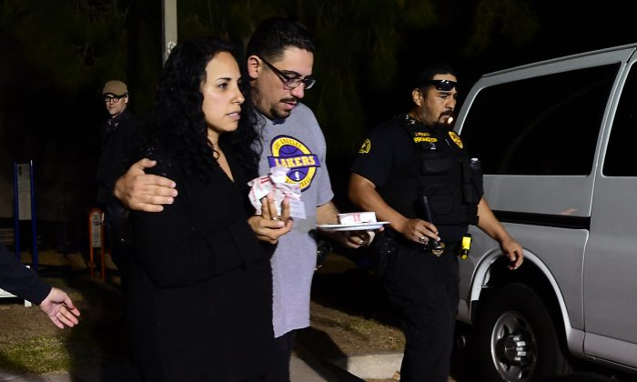 Omar Riopedre embraces his wife Diana, who was in the Inland Regional Center when the mass shootings took place, as they leave the Rudy C. Hernandez Community Center in the San Bernardino on December 2, 2015. (Frederic J. Brown/AFP/Getty Images)