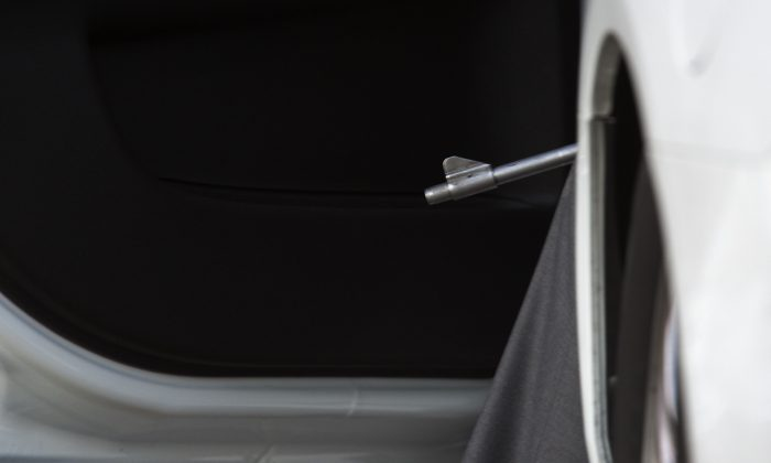 A gun barrel extends from the open door of an undercover police car during the seach for the California killers on December 2, 2015. (David McNew/Getty Images)