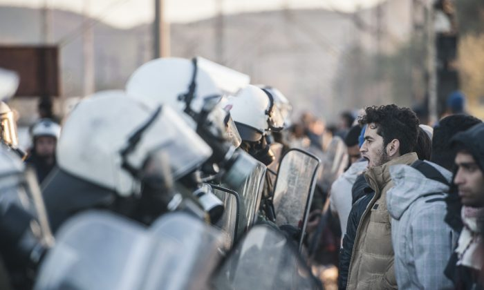 TOPSHOT - Stranded migrants and refugees stand in front of a Greek police cordon as they try to cross the Greek-Macedonian border near the village of Idomeni, Greece on December 3, 2015. Macedonia has restricted passage to northern Europe to only Syrian, Iraqi and Afghan nationals who are considered war refugees. All other nationalities are deemed economic migrants and told to turn back. Over 1,500 people are stuck on the border, mostly Indian, Moroccan, Bangladeshi and Pakistani.  / AFP / ARMEND NIMANI        (Photo credit should read ARMEND NIMANI/AFP/Getty Images)