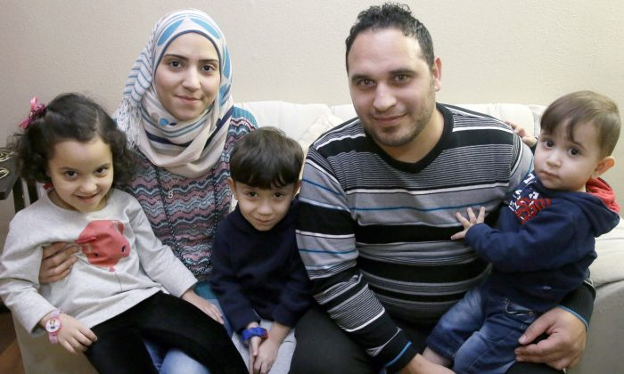 In this photo made Monday, Nov. 29, 2015, Syrian refugee Bashar al Jaddou, second from right, poses for a photo with his wife Maryam, second from left, and their children twins Maria, left, Hasan, center, and Mohammad word at their apartment in Dallas. (AP Photo/LM Otero)