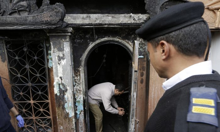 An Egyptian forensic member checks the gate of the nightclub which was attacked in Cairo, Egypt, Friday, Dec. 4, 2015. (AP Photo/Amr Nabil)